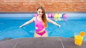 Девушка ослабляя на бассейне с питьем Стоковые Изображения