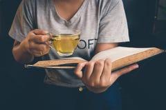 Девушка ослабляя прочитанный чай книги и питья горячий Стоковое фото RF