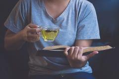 Девушка ослабляя прочитанный чай книги и питья горячий Стоковые Фотографии RF