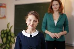 Девушка отвечает на вопросы учителей около школьного правления Стоковые Изображения
