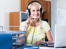 Девушка отвечая звонку службы технической поддержки и усмехаться стоковое изображение