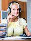 Девушка отвечая звонку службы технической поддержки и усмехаться стоковое фото rf
