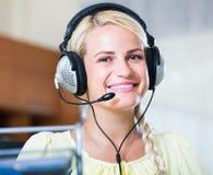Девушка отвечая звонку службы технической поддержки и усмехаться стоковая фотография