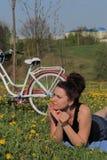 Девушка отдыхает на луге весны Лож на покрывале Рядом велосипед Одуванчики зацветают, молодая трава растут стоковые фотографии rf