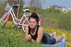 Девушка отдыхает на луге весны Лож на покрывале Рядом велосипед Одуванчики зацветают, молодая трава растут стоковое изображение