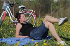 Девушка отдыхает на луге весны Лож на покрывале Рядом велосипед Одуванчики зацветают, молодая трава растут стоковое фото