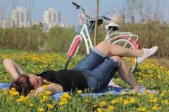 Девушка отдыхает на луге весны Лож на покрывале Рядом велосипед Одуванчики зацветают, молодая трава растут стоковая фотография rf
