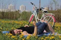 Девушка отдыхает на луге весны Лож на покрывале Рядом велосипед Одуванчики зацветают, молодая трава растут стоковое фото rf