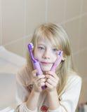 Девушка отжимает ее смотреть на 2 различных зубной щетки Стоковое фото RF