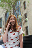 Девушка отправляя СМС на умном усаживании телефона Стоковая Фотография RF