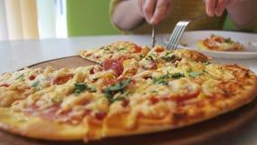Девушка отрезать пиццу на белой плите в ресторане на белом деревянном столе Съемка тележки видеоматериал