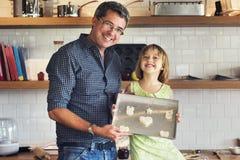 Девушка отца семьи делая печенья уча концепцию выпечки стоковые фото