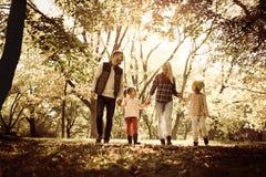 девушка отца семьи мальчика предпосылки обнимая его маленький супруга пруда парка мати человека Seasone в природе Стоковая Фотография