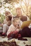 девушка отца семьи мальчика предпосылки обнимая его маленький супруга пруда парка мати человека Образование в природе Стоковые Изображения