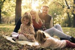 девушка отца семьи мальчика предпосылки обнимая его маленький супруга пруда парка мати человека Дайте образование и потеха Стоковые Изображения RF