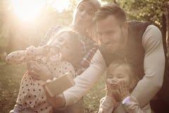 девушка отца семьи мальчика предпосылки обнимая его маленький супруга пруда парка мати человека Автопортрет Стоковое Изображение