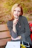 Девушка отдыхая в парке, на обеденном времени Женщина в влюбленности Женщина думает что написать Стоковое Фото