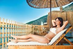 Девушка отдыхая на lounger солнца на пляже Стоковое Фото