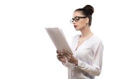 Девушка офиса в стеклах держит бумаги в руках изолированных на белизне Стоковое Изображение