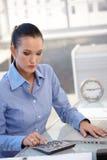 Девушка офиса используя калькулятор стоковое фото