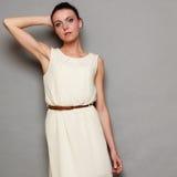Девушка очарования в белом платье на сером цвете Стоковые Фотографии RF