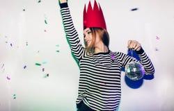Девушка партии в красочных фарах и confetti усмехаясь на белой предпосылке празднуя brightful событие, носят обнажанный Стоковая Фотография