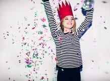 Девушка партии в красочных фарах и confetti усмехаясь на белой предпосылке празднуя brightful событие, носят обнажанный Стоковые Изображения
