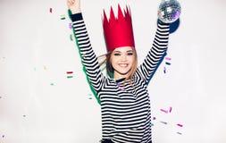 Девушка партии в красочных фарах и confetti усмехаясь на белой предпосылке празднуя brightful событие, носят обнажанный Стоковое Изображение