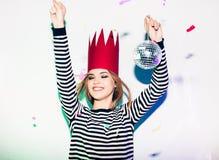 Девушка партии в красочных фарах и confetti усмехаясь на белой предпосылке празднуя brightful событие, носят обнажанный Стоковое Фото