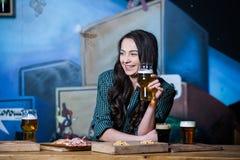 Девушка партии Пиво красивой девушки выпивая девушка брюнет провозглашать и есть в пабе Стоковая Фотография