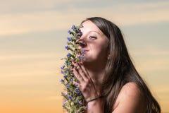Девушка пахнуть цветком на заходе солнца Стоковые Фотографии RF