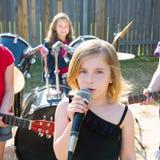 Девушка певицы детей поя играющ диапазон в реальном маштабе времени в задворк Стоковые Фотографии RF
