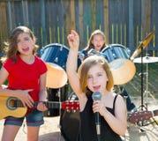 Девушка певицы детей поя играющ диапазон в реальном маштабе времени в задворк Стоковое фото RF