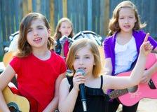 Девушка певицы детей поя играющ диапазон в реальном маштабе времени в задворк Стоковые Изображения RF