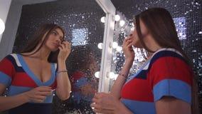 Девушка перед красивым зеркалом делает ее макияж 4K медленный Mo акции видеоматериалы