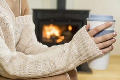 Девушка перед камином в носках зимы Стоковые Изображения