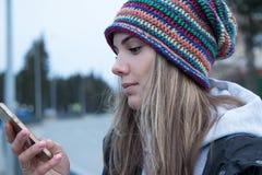 Девушка пестротканая striped шляпа смотрит на мобильном телефоне Стоковые Изображения