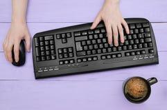 Девушка печатает на черной клавиатуре и держит мышь Offee ¡ Ð с пеной в черной чашке Фиолетовая деревянная предпосылка стоковая фотография rf