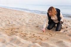 Девушка писать Новый Год в песке Стоковая Фотография