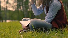 Девушка пишет личный дневник в парке акции видеоматериалы
