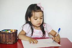 Девушка пишет на бумаге Стоковое Изображение