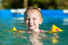 Девушка плавает в бассейне в подушках Стоковая Фотография