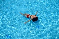 Девушка плавает в бассейне стоковые фото