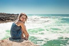 девушка платья над усаживанием моря утеса Стоковая Фотография