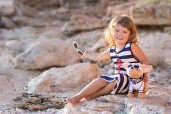 Девушка пляжа милая представляя на скалистом пляже босоногом со стеклами платья и солнца матроса вьющиеся волосы нося стоковые фото