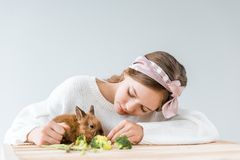 Девушка подавая милый меховой кролик с брокколи на деревянном столе Стоковые Фото