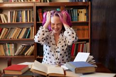 Девушка подготавливает для книги чтения экзамена в библиотеке утомлена Стоковое Изображение