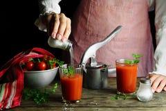 Девушка подготавливает сок томата с солью Стоковая Фотография