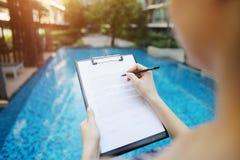 Девушка подписывает бумагу против предпосылки бассейна солнечного дня лета Фронт используемый с открытой лицензией шрифта Стоковые Фото