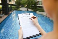 Девушка подписывает бумагу против предпосылки бассейна солнечного дня лета Fr Стоковое Изображение